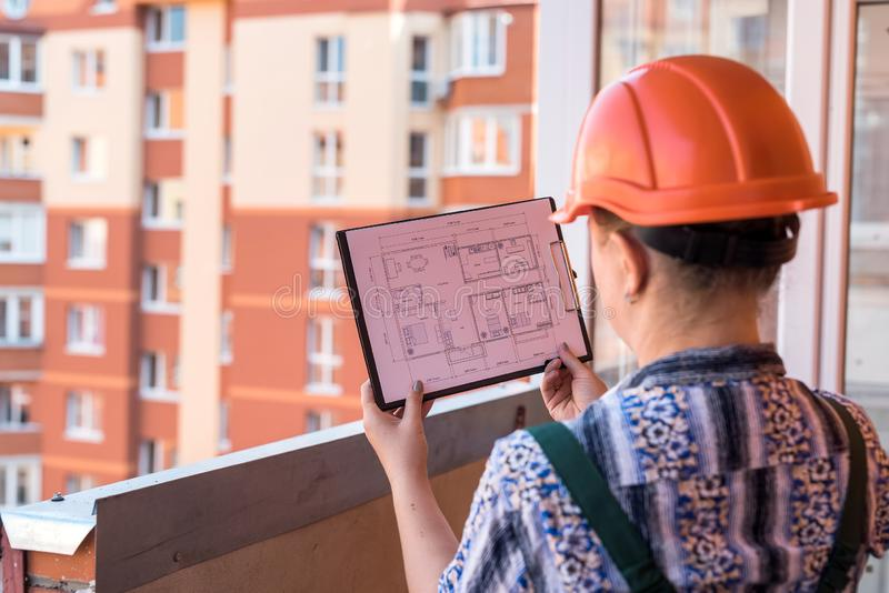 Woman in uniform looking at house plan on construction site.  royalty free stock photo