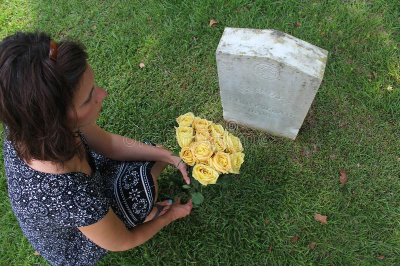 Woman at Unknown soldier`s grave with yellow flowers. stock image