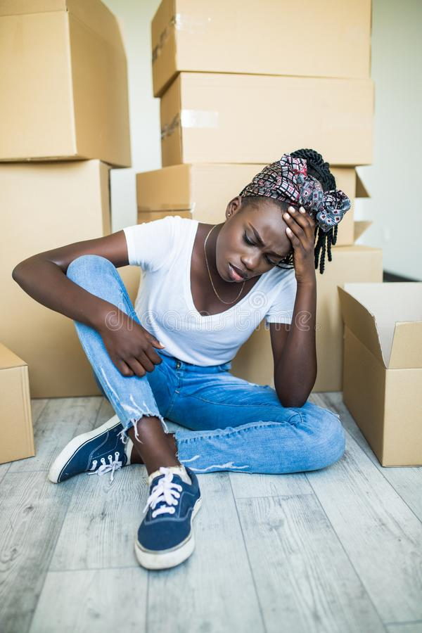 Sad african Woman unlimitedly happy because of moving new house of her dream, sitting on the floor with lots of cardboard boxes royalty free stock images