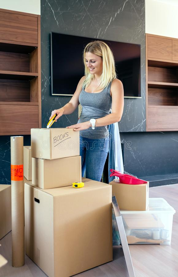 Woman unpacking moving boxes royalty free stock images