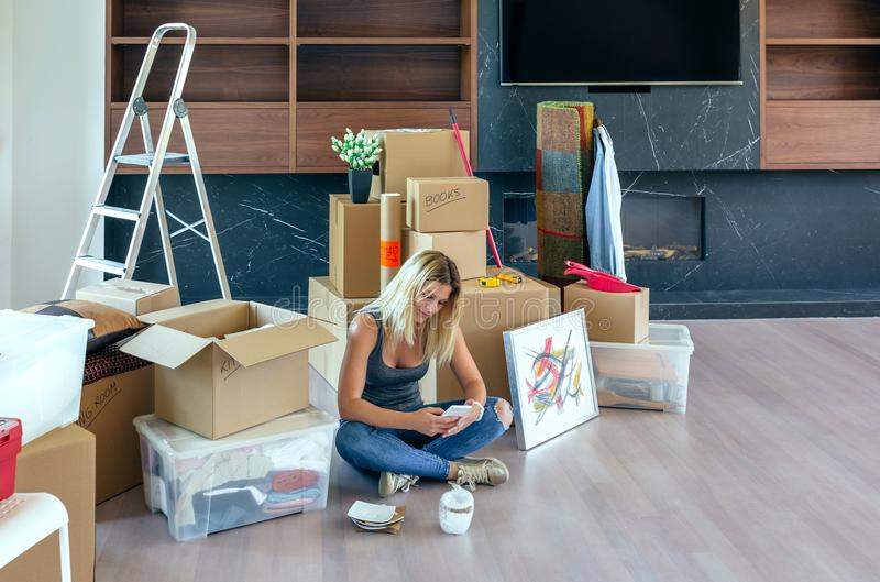 Woman unpacking moving boxes. And looking cell phone stock photos