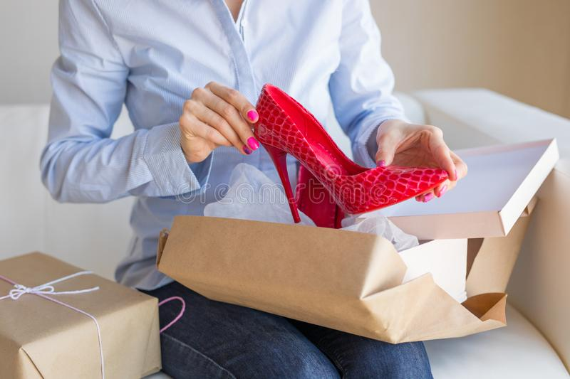 Woman unpacking new shoes delivered by post. While sitting in sofa stock images