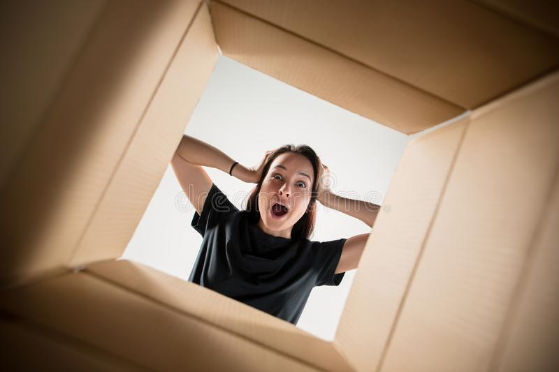 Woman unpacking and opening carton box and looking inside royalty free stock image