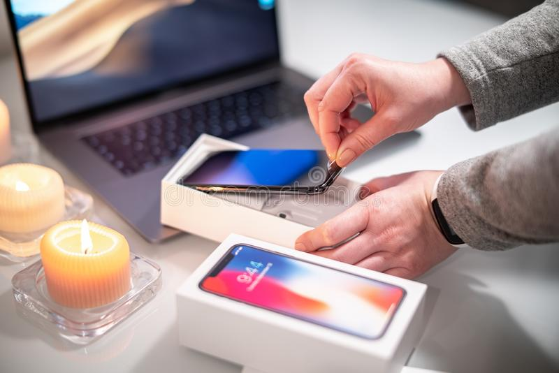 Woman unpacks a new space gray smartphone. Woman unpacks a new space gray smartphone royalty free stock photos