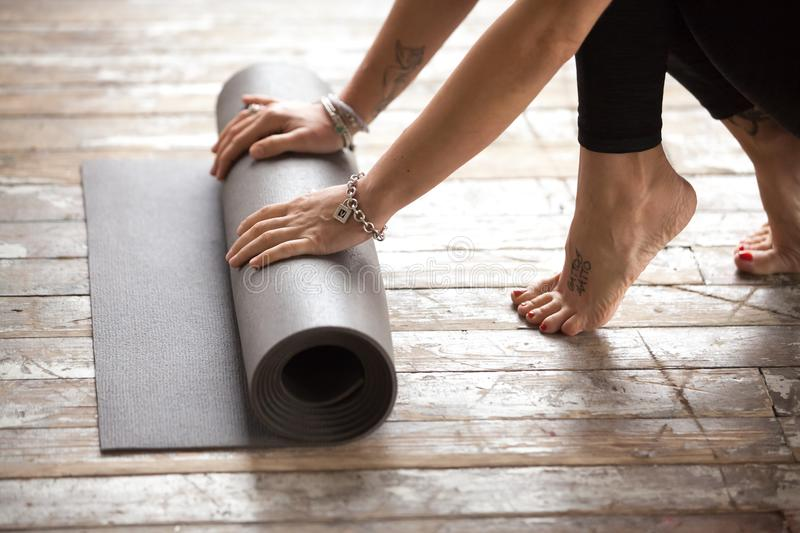 Woman unrolling exercise mat to begin fitness practice. Hands of young fit woman stretching out black exercise yoga mat before working out at home in living room stock photos