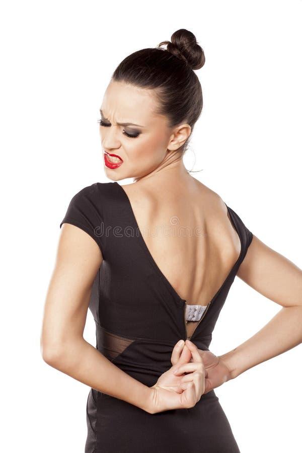 Woman unzipping her dress stock image