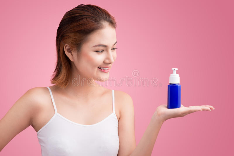 Woman use body lotion on arms and holding cosmetics bottle stock images
