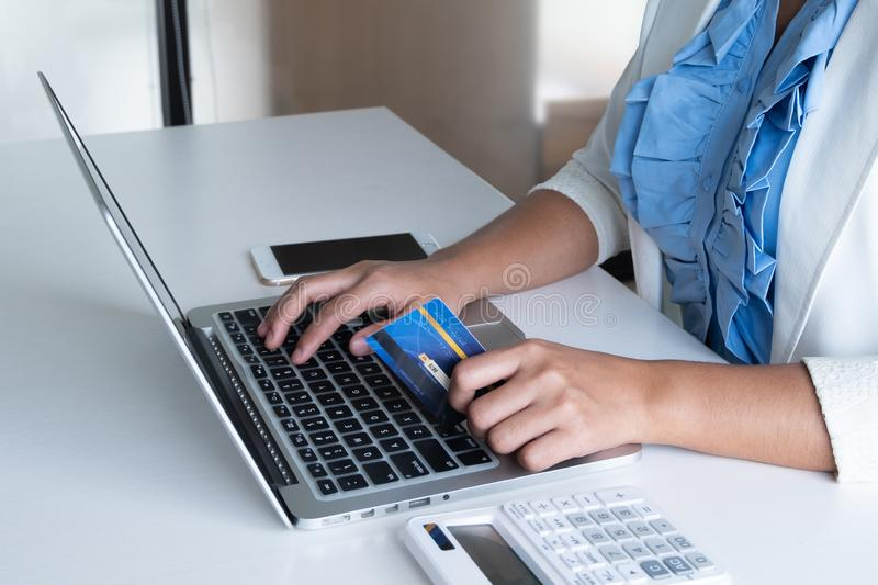 Woman use credit card for online shopping on her laptop and phone royalty free stock image