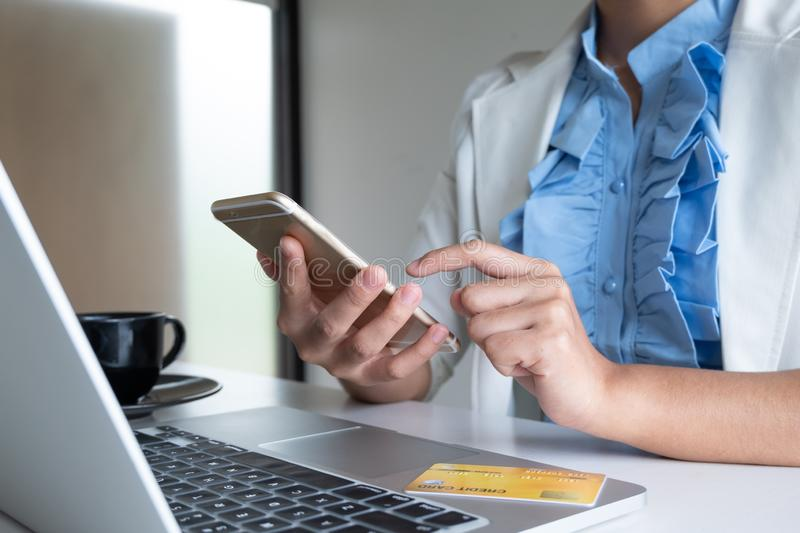 Woman use credit card for online shopping on her laptop and phone royalty free stock photography