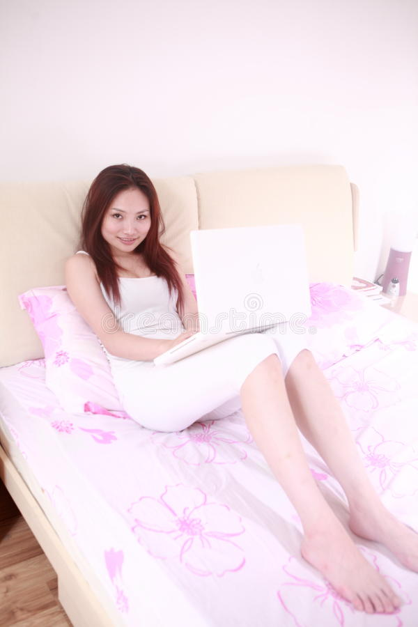 Woman use laptop on bed royalty free stock images