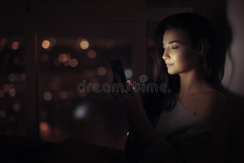 Woman use of mobile phone indoors at night stock images