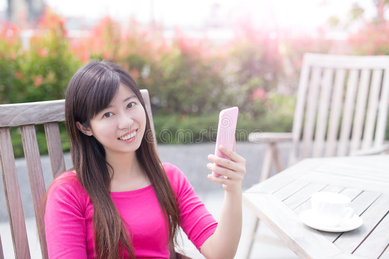 Woman use phone. Ans smile happily in the park royalty free stock images