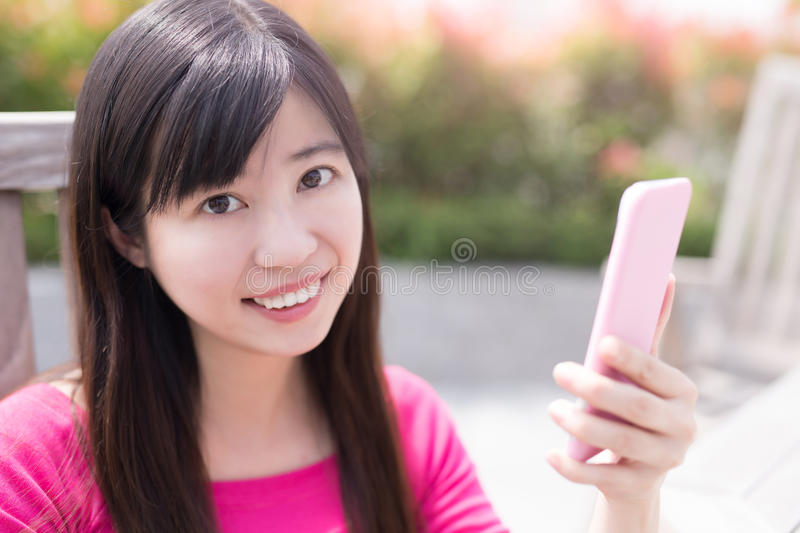 Woman use phone. Ans smile happily in the park stock images
