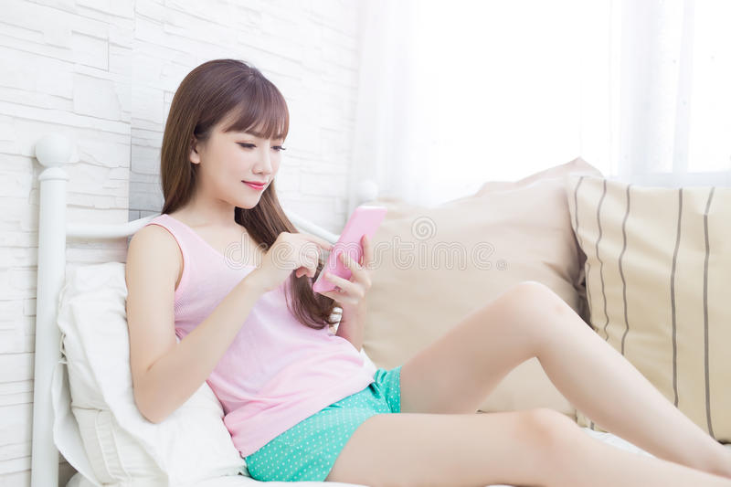Woman use phone. Beauty woman use phone on the bed royalty free stock image