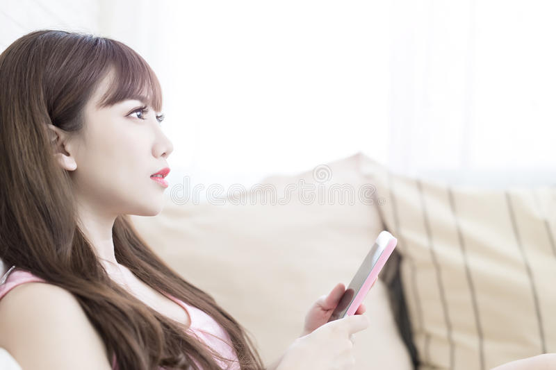 Woman use phone. Beauty woman use phone on the bed stock image