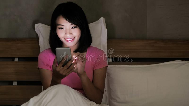 Woman use phone. Happily on the bed in the evening royalty free stock photo