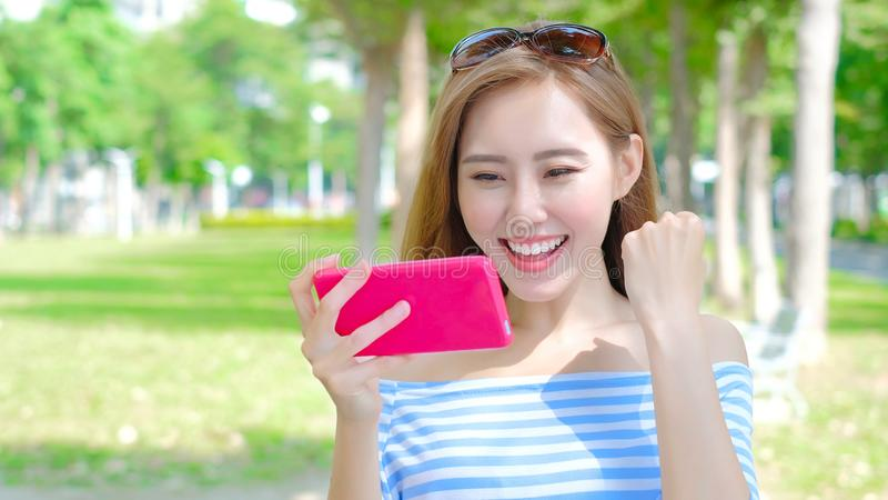 Woman use phone. Woman play phone and mobile game in the park royalty free stock photography
