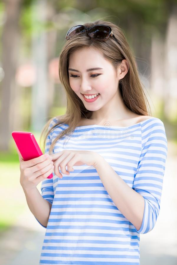 Woman use phone. Woman smile and use phone in the park royalty free stock photo