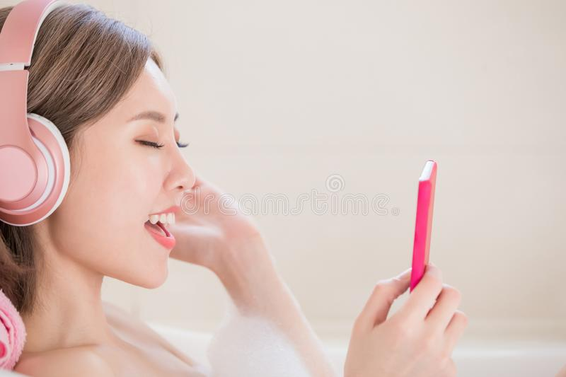 Woman listen music in bathtub. Woman use phone and wear headphone listen music in bathtub royalty free stock photography
