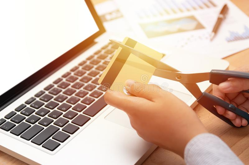 Woman use scissors to cut credit cards in hand in front of computer laptop. royalty free stock image