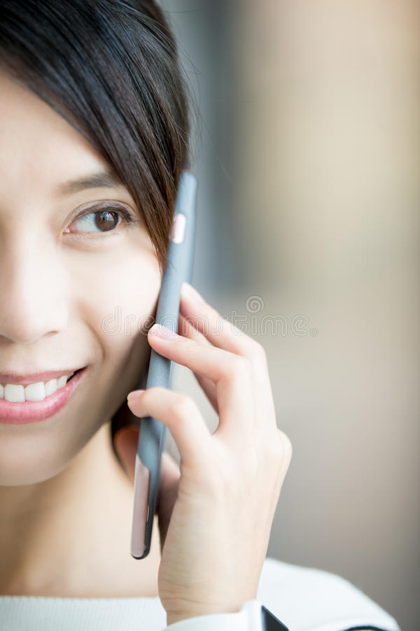 Woman use smart phone. Half face of Happy woman speak and use smart phone outdoor, asian beauty royalty free stock photography
