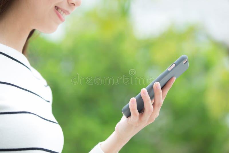 Woman use smart phone. Happy woman use smart phone outdoor, asian beauty stock photo