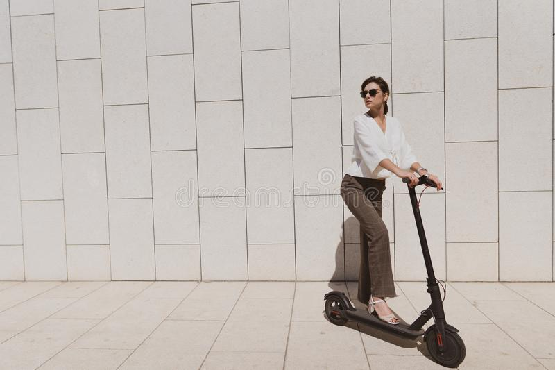 A woman uses an electric scooter in a park. The new gadget for fast movement around the city without traffic jams stock images