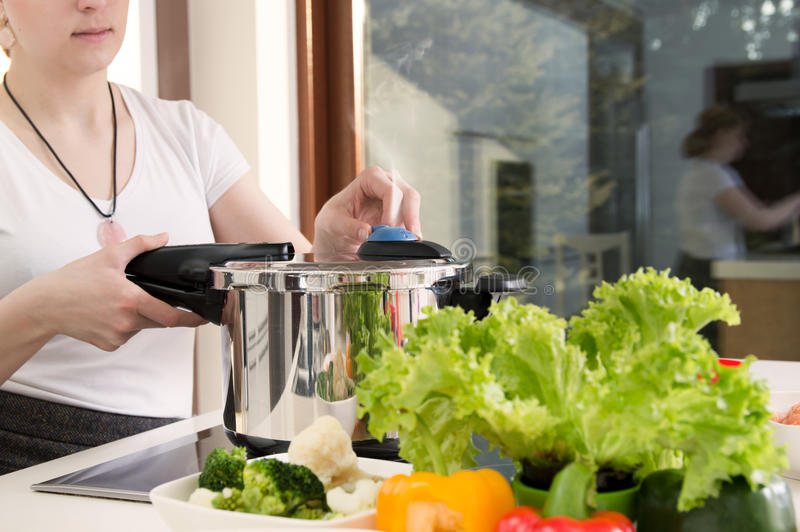 Woman uses pressure cooker to cook a meal. stock photo