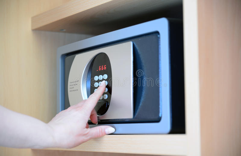 woman uses a safe in hotel stock image