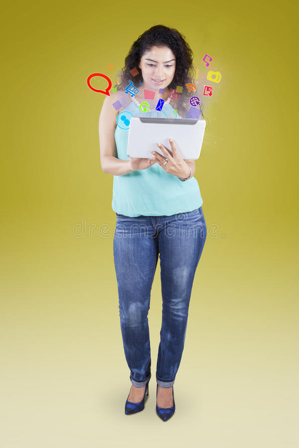 Woman uses tablet with social media icons stock photo