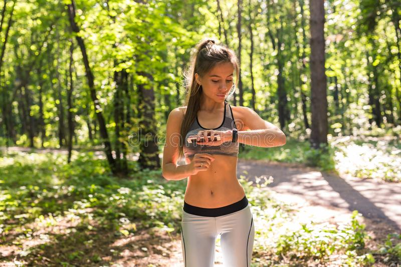 Woman using activity tracker or heart rate monitor. Outdoor fitness concept. Woman using activity tracker or heart rate monitor. Outdoor fitness concept royalty free stock photo