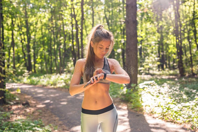Woman using activity tracker or heart rate monitor. Outdoor fitness concept. Woman using activity tracker or heart rate monitor. Outdoor fitness concept stock image