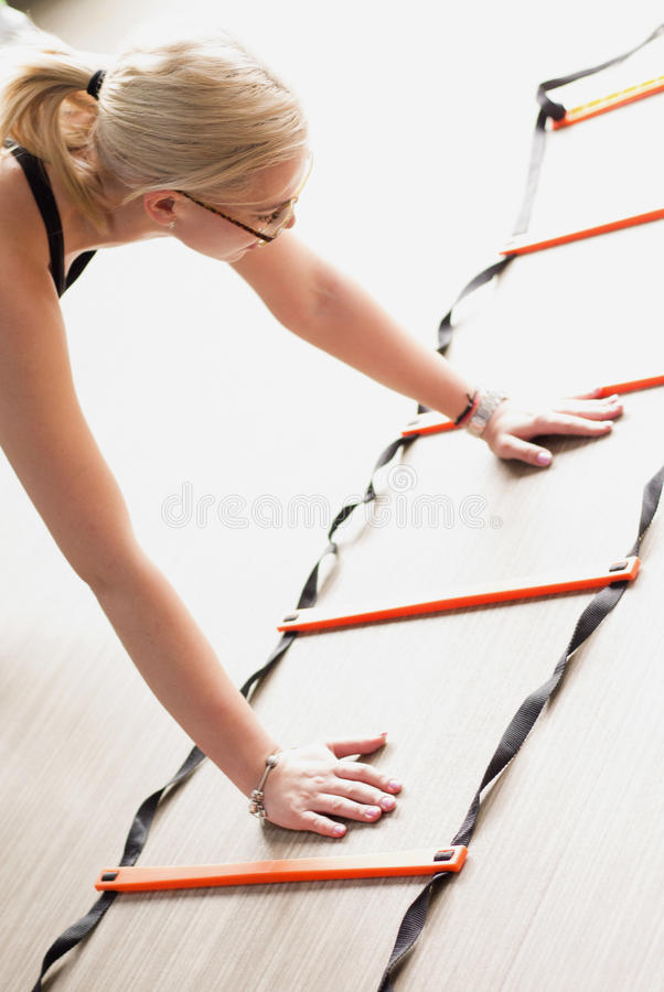 Woman using agility ladder. Agility ladder in use during fitness class royalty free stock image