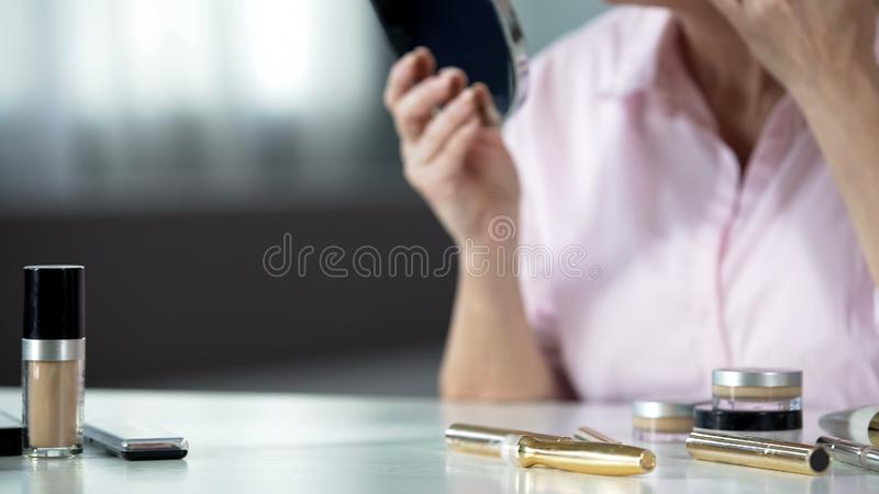 Woman using anti-aging cosmetics for wrinkled skin care, desire to be beautiful. Stock photo royalty free stock photos