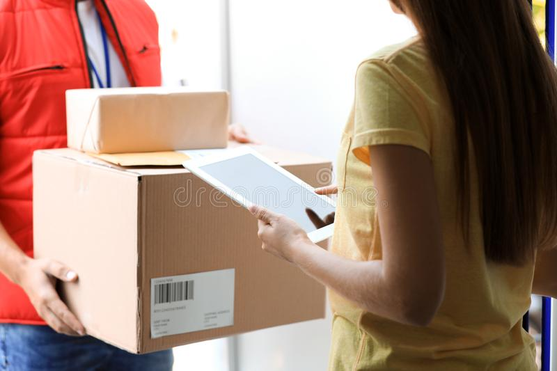 Woman using app to confirm delivery of parcel from courier on doorstep. Closeup royalty free stock images