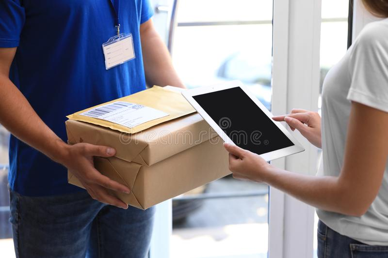 Woman using app to confirm delivery of parcel from courier on doorstep. Closeup stock images