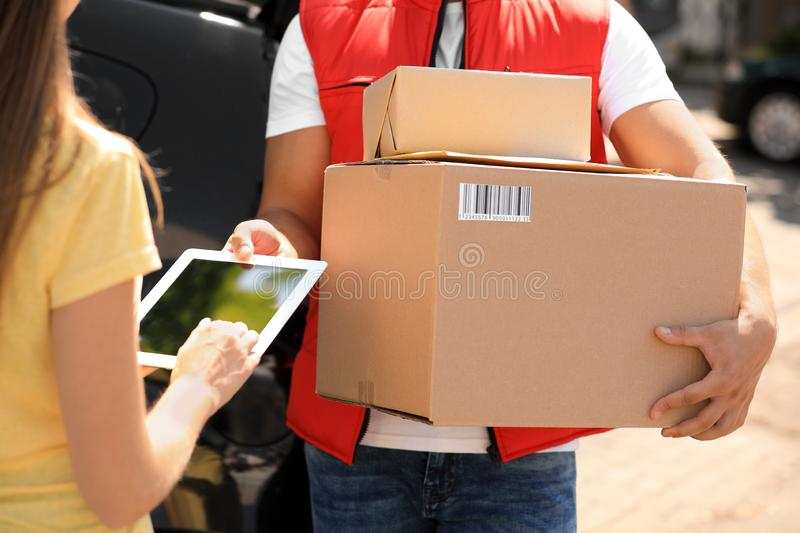 Woman using app to confirm delivery of parcel from courier outdoors. Closeup stock image