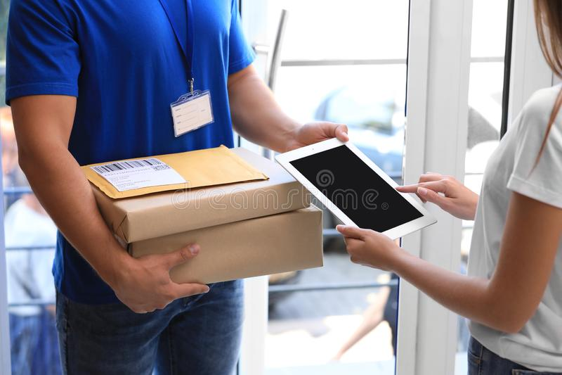 Woman using app to confirm delivery of parcels from courier on doorstep. Closeup stock photo