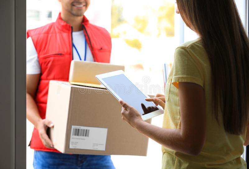 Woman using app to confirm delivery of parcels from courier on doorstep. Closeup royalty free stock images
