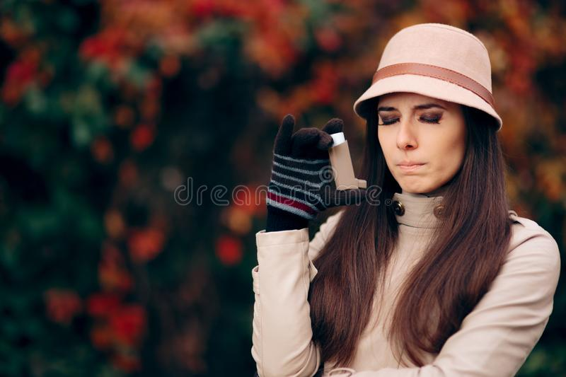 Woman Using Asthma Inhaler in Autumn Season stock images