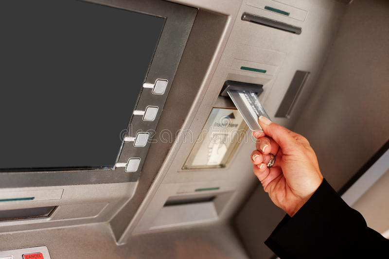 Woman using an ATM. Cropped view of a female hand inserting a bank card into an ATM to begin a financial transaction stock image
