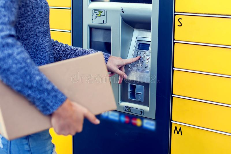 Woman using automated self service post terminal machine or lock. Woman client using automated self service post terminal machine or locker to deposit the parcel stock photos