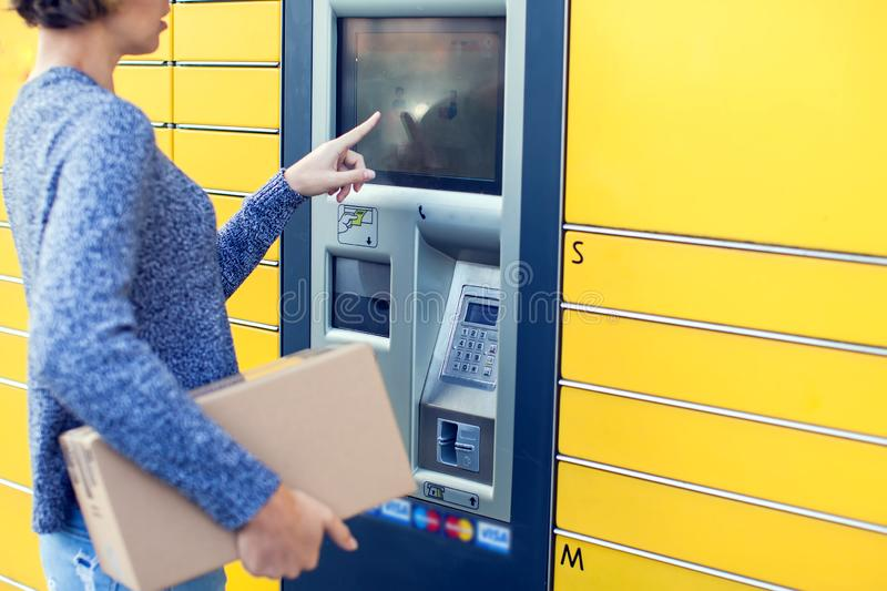 Woman using automated self service post terminal machine or lock. Woman client using automated self service post terminal machine or locker to deposit the parcel stock photography