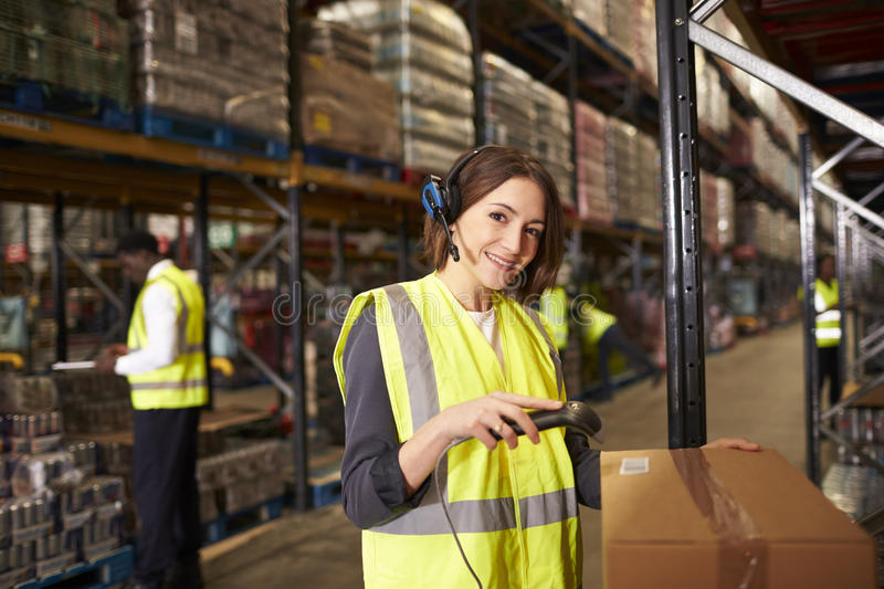 Woman using a barcode reader in a warehouse looks to camera royalty free stock photo