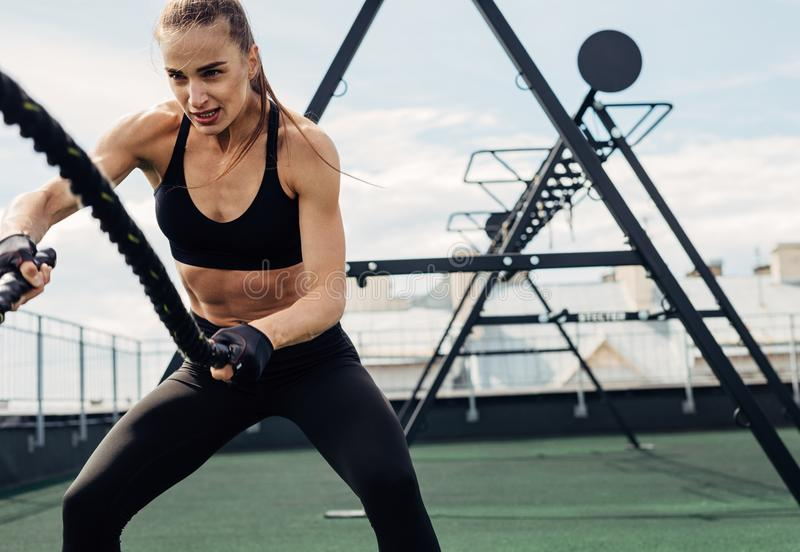 Woman using battle ropes during strength training on rooftop stock photo
