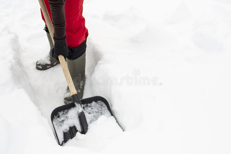 Woman using black plastic shovel with a wooden handle makes the stock photo