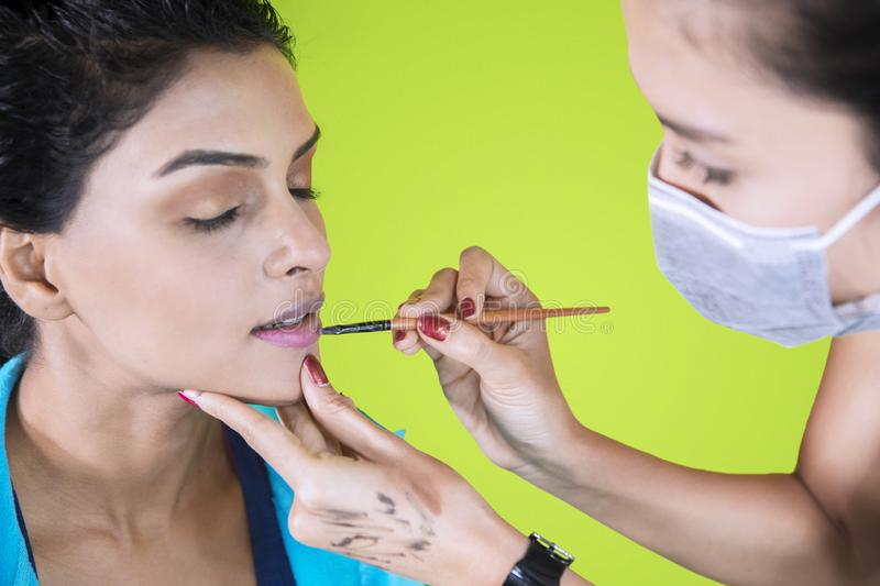 Woman using a brush to apply lipstick to her client stock photos