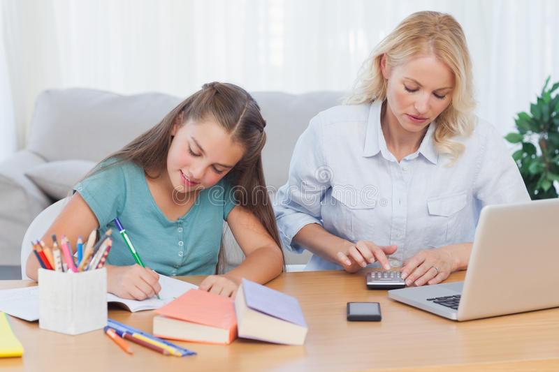 Download Woman Using Calculator At Desk In Living Room Stock Photo - Image: 32232510