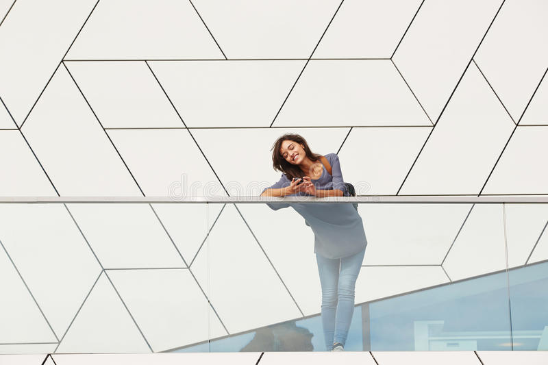 Woman using cell phone. Portrait of young urban woman leaning to railing outdoors and using cell phone royalty free stock photography