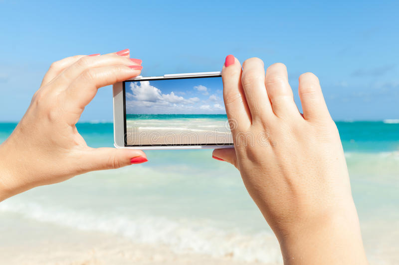 Woman using cell phone for taking sea landscape photo royalty free stock photography